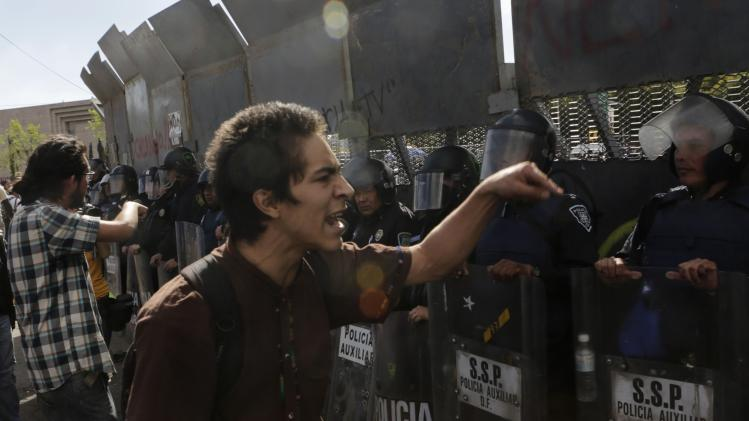 Protesters shout against riot policemen standing guard outside the lower house in Mexico City