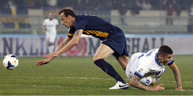 Inter Milan's Mauro Icardi, right, is fouled by Hellas Verona Greek defender Evangelos Moras during a Serie A soccer match at the Bentegodi stadium in Verona, Italy, Saturday, March 15, 2014