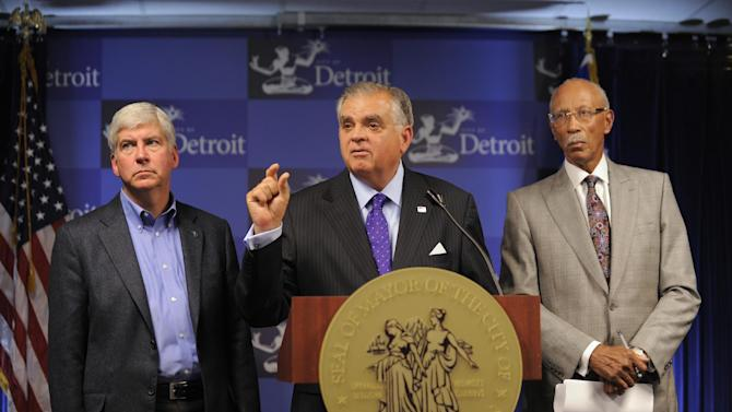 "Michigan Governor Rick Snyder,left,  US Secretary of Transportation Ray LaHood, center, and Detroit Mayor Dave Bing discussing the status of the regional transit authority and bringing light rail to downtown Detroit during a press conference at the Mayor's office, Oct. 15, 2012.  ""We're this close"", said LaHood when responding to a reporter's question about the status of the deal.    (AP Photo/Detroit News, David Guralnick)  DETROIT FREE PRESS OUT; HUFFINGTON POST OUT"