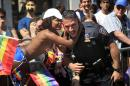 Tina Hitscherich surprises a police officer with a kiss during the NYC Pride Parade in New York, Sunday, June 26, 2016. With a moment of silence followed by the roar of motorcycles, New York City's gay pride parade kicked off Sunday, a celebration of barriers breached and a remembrance of the lives lost in the massacre at the gay nightclub in Orlando. (AP Photo/Seth Wenig)