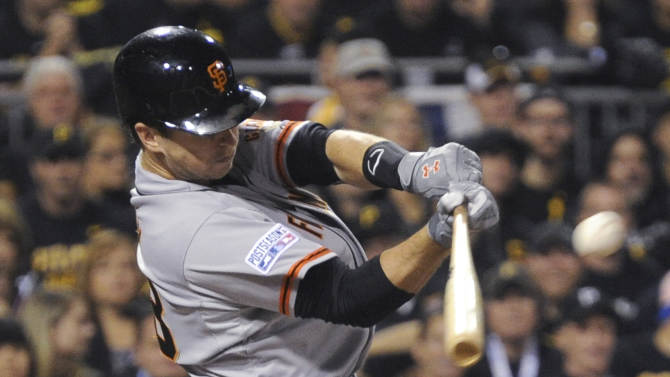 San Francisco Giants' Buster Posey hits a fly ball to deep center field, where Pittsburgh Pirates center fielder Andrew McCutchen caught it for an out in the first inning of the NL wild-card playoff baseball game Wednesday, Oct. 1, 2014, in Pittsburgh. (AP Photo/Don Wright)