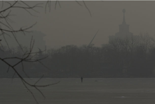 A man walks on an frozen lake on a hazy day in Beijing, China, Monday, Jan. 14, 2013. Beijing schools kept children indoors and hospitals saw a spike in respiratory cases Monday following a weekend of