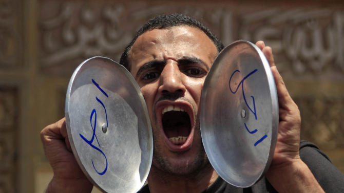 """An opponent of Egypt's Islamist President Mohammed Morsi chants slogans as he holds pot covers with Arabic that reads, """"leave,"""" during a protest outside the presidential palace, in Cairo, Egypt, Sunday, June 30, 2013. Thousands of Egyptians demanding the ouster of Morsi are gathering at Cairo's central Tahrir Square and the presidential palace at the start of a day of massive, nationwide protests many fear could turn deadly. (AP Photo/Khalil Hamra)"""