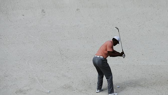 Tiger Woods chips out of bunker on the fourth hole during a practice round for the Masters golf tournament Tuesday, April 9, 2013, in Augusta, Ga. (AP Photo/Matt Slocum)