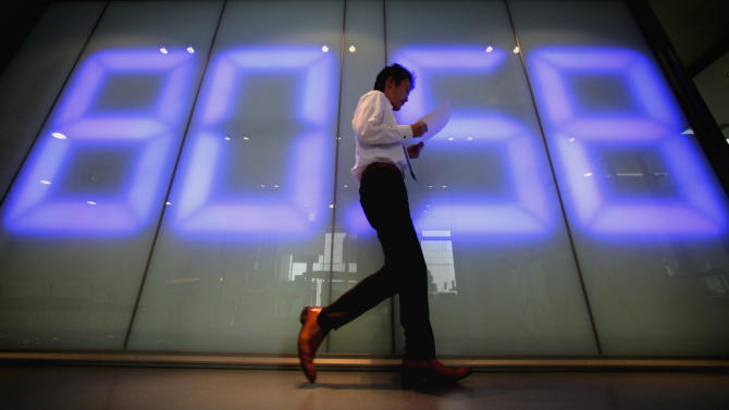 A money trader walks past a large screen displaying an exchange rate for the U.S. dollar to Japanese yen at a foreign exchange firm in Tokyo Friday, Oct. 29, 2010. The dollar slumped to the 80 yen level, nearing a post World War II record low of 79.75 yen set in 1995. (AP Photo/Itsuo Inouye)