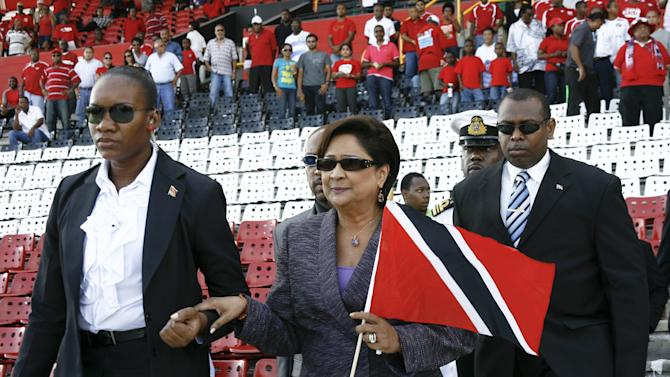 The Prime Minister of Trinidad and Tobago, Kamla Persad-Bissessar (C), holds a national flag as she arrives for the presentation of the teams before the start  of the 2014 Brazil World Cup qualifier match between Trinidad and Tobago and Bermuda, in Port of Spain, on September 2, 2011.   AFP PHOTO/Frederic DUBRAY (Photo credit should read Frederic Dubray/AFP/Getty Images)