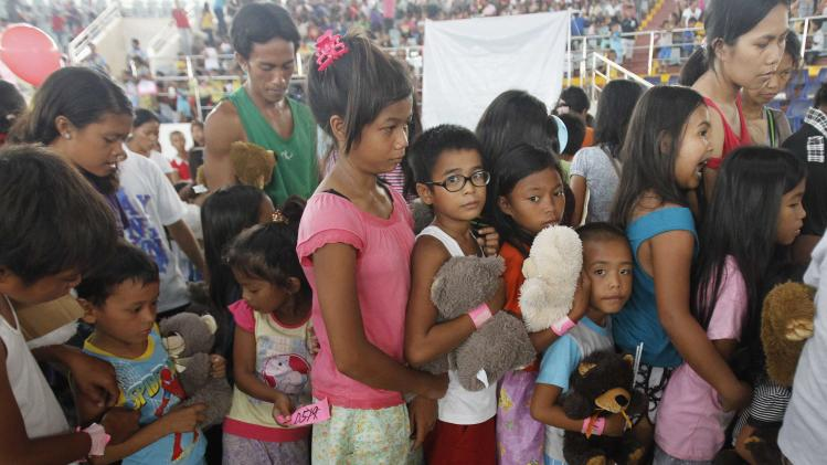 Survivors of super Typhoon Haiyan queue during a gift giving activity inside a astrodome at Tacloban