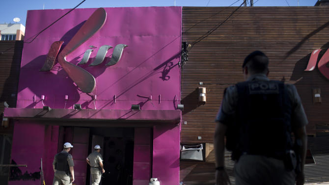 Police officers enter the Kiss nightclub in Santa Maria city, Rio Grande do Sul state, Brazil, Monday, Jan. 28, 2013. A fast-moving fire roared through the crowded, windowless Kiss nightclub in this southern Brazilian city early Sunday, killing more than 230 people. Many of the victims were under 20 years old, including some minors.(AP Photo/Felipe Dana)