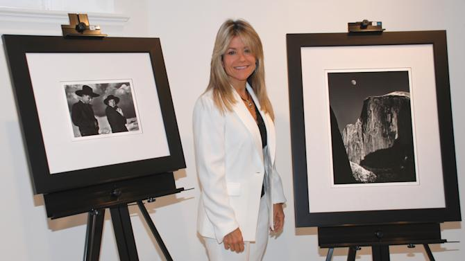 """In this photo provided by the College of New Rochelle, Judith Huntington, president of The College of New Rochelle, is flanked by two Ansel Adams photographs at the school in New Rochelle, Tuesday, Oct. 9, 2012. The two photos are from a  collection of 75 signed Ansel Adams photographs, valued at $2.5 million, that were a gift to the school.  At left is """"Georgia O'Keefe and Orville Cox, Canyon de Chellly National Monument, Arizona, 1937,""""  and at right  """"Moon and Half Dome, Yosemite National Park, California, 1960."""" (AP Photo/College of New Rochelle)"""