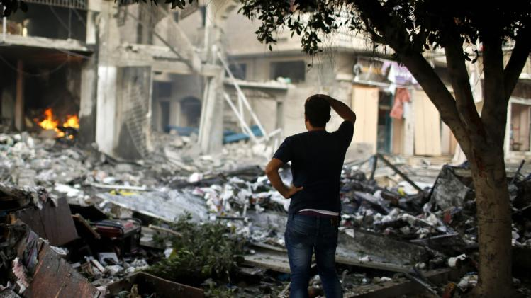 A Palestinian man looks at a house which police said was hit in an Israeli air strike, in Gaza City
