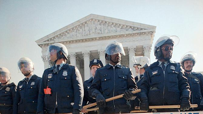 FILE - In this Tuesday, Oct 13, 1987 file photo, gay activists attempt to block the steps of the Supreme Court as part of an act of civil disobedience in Washington, two days after the Gay March on Washington, as police stand guard to block an attempt by the group to enter the building. In late June 2013, the Supreme Court is expected to rule in two cases involving same-sex marriage. One is a challenge to California's voter-approved Proposition 8 that defines marriage as the union of a man and a woman. The other seeks to strike down a portion of the federal Defense of Marriage Act that denies to legally married same-sex couples a range of benefits that generally are available to married heterosexuals. (AP Photo/J. Scott Applewhite)