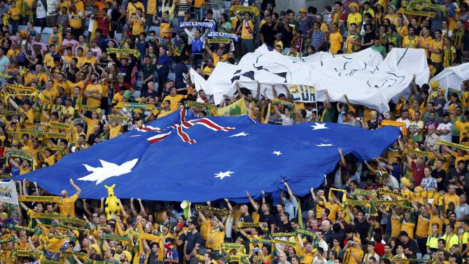 Australia's fans hold a giant flag before their Asian Cup final soccer match against South Korea at the Stadium Australia in Sydney