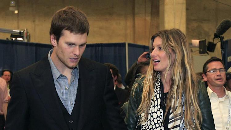 New England Patriots quarterback Tom Brady and his wife, supermodel Gisele Bundchen, leave the stadium after the Patriots lost 21-17 to the New York Giants in the NFL Super Bowl XLVI football game, Sunday, Feb. 5, 2012, in Indianapolis. (AP Photo/Mark Humphrey)