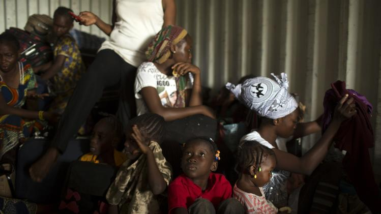 Women and children sit inside a container truck as they wait to depart to the west of the country towards the border with Cameroon, as they flee sectarian violence in Bangui