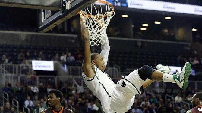 Michigan State's Adreian Payne (5) celebrates while hanging on the rim after dunking the basketball during the first half of a Coaches vs. Cancer NCAA college basketball game against the Virginia Tech, Friday, Nov. 22, 2013, in New York. (AP Photo/Frank Franklin II)