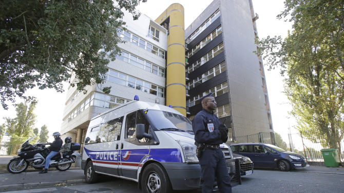 """A French policeman stands guard outside the headquarters of the satirical weekly Charlie Hebdo in Paris, Wednesday, Sept. 19, 2012. Police took up positions outside the Paris offices of the satirical French weekly that published crude caricatures of the Prophet Muhammad on Wednesday that ridicule the film and the furor surrounding it. The provocative weekly, Charlie Hebdo, was firebombed last year after it released a special edition that portrayed the Prophet Muhammad as a """"guest editor"""" and took aim at radical Islam. (AP Photo/MIchel Euler)"""