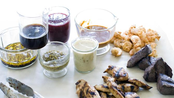 This July 29, 2013 photo shows, from left, marinades of garlic balsamic, maple soy, lemon herb, raspberry ginger, white wine mustard and orange cumin in Concord, N.H. On the meat, from top, are chipolte lime, red wine and rosemary and spicy hoisin. (AP Photo/Matthew Mead)