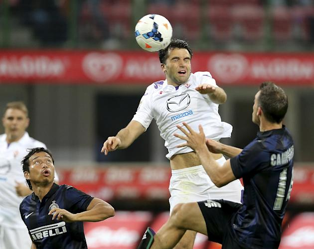 Fiorentina forward Giuseppe Rossi, center, jumps for the ball with Inter Milan defender Hugo Campagnaro, right, of Argentina, and Inter Milan defender Yuto Nagatomo, of Japan, during the Serie A socce