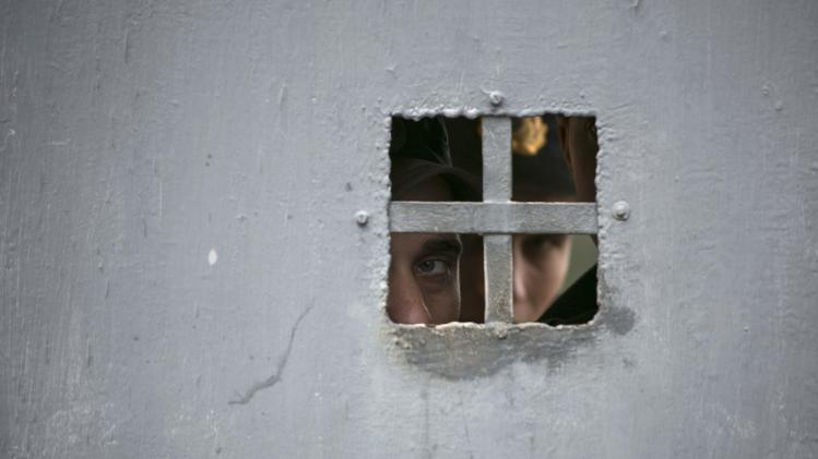 Ukrainian servicemen look out of the gate of their military base near Sevastopol