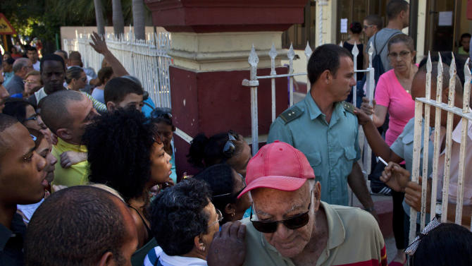People line up at a migration office in Havana, Cuba, Monday, Jan. 14, 2013. Cubans formed long lines outside travel agencies and migration offices, as a highly anticipated new law took effect Monday, ending the island's much-hated exit visa requirement. The measure means the end of both real and symbolic obstacles to travel by islanders, though it is not expected to result in a mass exodus. Most Cubans are now eligible to leave with just a current passport and national identity card, just like residents of other countries. (AP Photo/Ramon Espinosa)