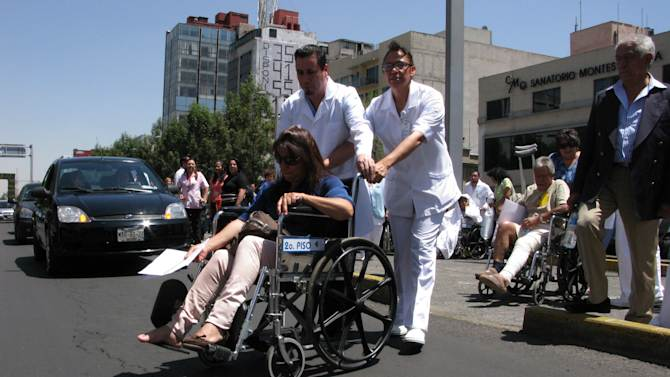 Patients are evacuated in wheelchairs from the Hospital de Chalpultepec after an earthquake was felt in Mexico City, Tuesday March 20, 2012.  A strong, long earthquake with epicenter in Guerrero state shook central southern Mexico on Tuesday, swaying buildings in Mexico City and sending frightened workers and residents into the streets. (AP Photo/Marco Ugarte)