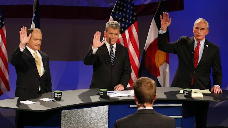 Colorado Republican gubernatorial hopefuls, left to right, former state Sen. Mike Kopp, Colorado Secretary of State Scott Gessler, and former Rep. Bob Beauprez answer yes to a question about fighting recent state gun legislation by raising their hands during a debate hosted by 9NEWS, in Denver, Thursday April 24, 2014. A fourth candidate, former U.S. Rep. Tom Tancredo, chose not to participate in the debate. The GOP primary is in June. (AP Photo/Brennan Linsley)