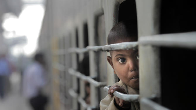A boy looks out from the window of a train at a railway station in New Delhi, India, Wednesday, March 14, 2012. India's railway minister unveiled the annual budget Wednesday for the railway network which is one of the world's largest, with some 14 million passengers daily.  (AP Photo/ Manish Swarup)