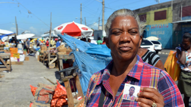 In this April 13, 2013 photo, Claudette Johnson shows a photo of her slain son Tyrone Johnson, who was 21 when he was killed, as she poses for a photo at the market in West Kingston, Jamaica.  Johnson still has a hard time sleeping at night a decade after her son was fatally shot in a confrontation with Jamaican police and 15 years after her taxi driver husband was murdered by gunmen. Year after year, both cases have collected dust in the island's gridlocked court system, leaving her in limbo. (AP Photo/David McFadden)