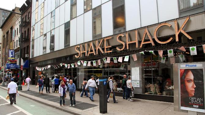 FILE - In this May 21, 2014, file photo, pedestrians walk by a Shake Shack in New York's theater district. Hamburger chain Shake Shack Inc. has priced its initial public stock offering at $21 per share, above its proposed range of $17 to $19 per share. (AP Photo/Mark Kennedy, File)