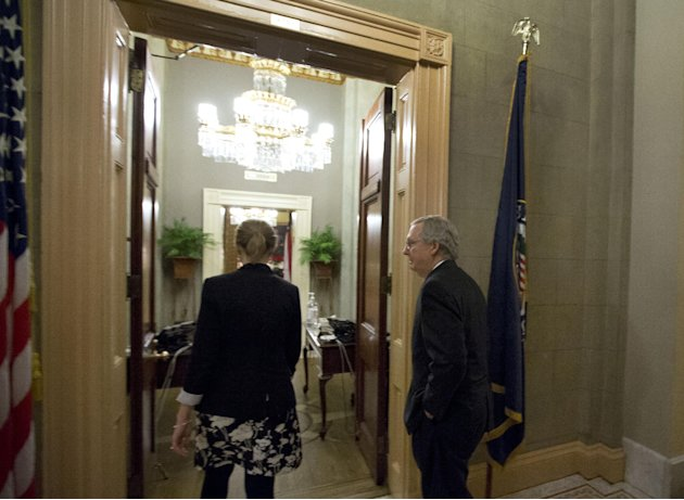Senate Minority Leader Mitch McConnell, right, from Kentucky, heads into his office after a vote on the fiscal cliff, on Capitol Hill Tuesday, Jan. 1, 2013 in Washington. The Senate passed legislation