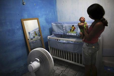 Daniele Santos holds her son Juan Pedro who is 2-months old and born with microcephaly at their house in Recife