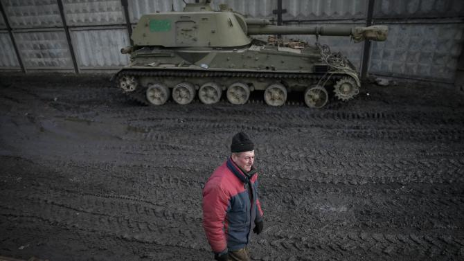 Member of Ukrainian armed forces walks near a self-propelled howitzer before loading it onto a wagon of a cargo train at a train station in Artemivsk