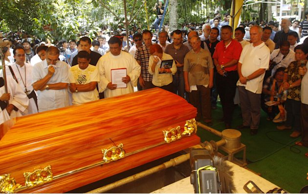 FILE - In this Oct. 25, 2011 file photo, a crowd gather in Kidapawan township as slain Italian priest Rev. Fausto Tentorio is laid in a coffin to rest in North Cotabato province in southern Philippine