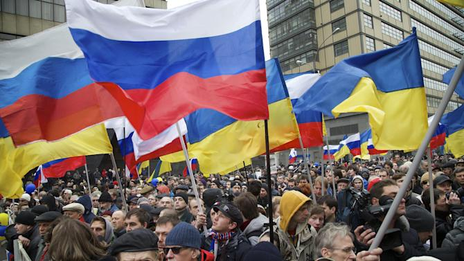Demonstrators hold Russian and Ukrainian flags during a massive rally to oppose president Vladimir Putin's policies in Ukraine, in Moscow, Saturday, March 15, 2014. Large rival marches have taken place in Moscow over Kremlin-backed plans for Ukraine's province of Crimea to break away and merge with Russia. More than 10,000 people turned out Saturday for a rally in the center of the city held to oppose what many demonstrators described as Russia's invasion of the Crimean Peninsula. In a nearby location, a similar sized crowd voiced its support for Crimea's ethnic Russian majority, who Moscow insists is at threat from an aggressively nationalist leadership now running Ukraine. (AP Photo/Alexander Zemlianichenko) (AP Photo/Alexander Zemlianichenko)