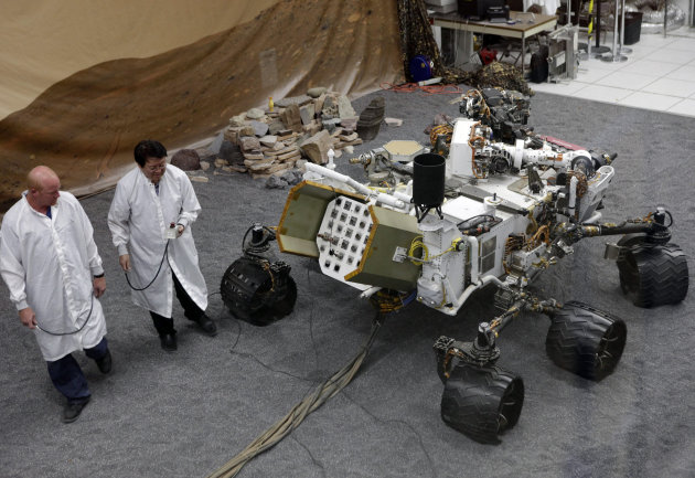 Engineers work on a model of the Mars rover Curiosity at the Spacecraft Assembly Facility at NASA&#39;s Jet Propulsion Laboratory in Pasadena, Calif., Thursday, Aug. 2, 2012. After traveling 8 1/2 months and 352 million miles, Curiosity will attempt a landing on Mars the night of Aug. 5, 2012. (AP Photo/Damian Dovarganes)