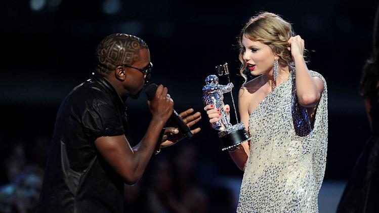 Kanye West takes the microphone from Taylor Swift and speaks onstage during the 2009 MTV Video Music Awards at Radio City Music Hall on September 13, 2009 in New York City.