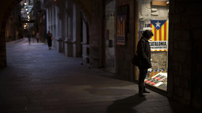 "In this photo taken on Monday, Nov. 19, 2012, a woman looks into at a shop window decorated with the ""estelada"" flag, a symbol of Catalonia's independence, in Girona, Spain. Catalonia holds elections on Sunday that will be seen as a test of the regional government's plans to hold a referendum on independence, and one of the key issues emerging is the theoretical place of a free Catalonia in Europe. (AP Photo/Emilio Morenatti)"