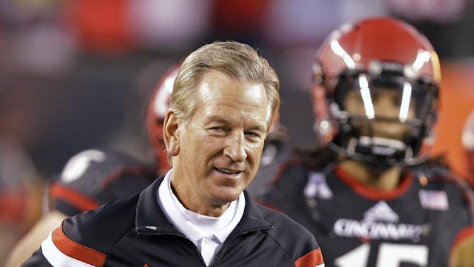 Cincinnati coach Tommy Tuberville runs onto the field at the start of an NCAA college football game against South Florida, Friday, Oct. 24, 2014, in Cincinnati