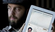 Martin Reisch holds up his iPad displaying his passport in Montreal, Tuesday, Jan. 3, 2012. Reisch was allowed entry into the United States using a scanned copy of his passport on his iPad. (AP Photo/The Canadian Press, Graham Hughes)
