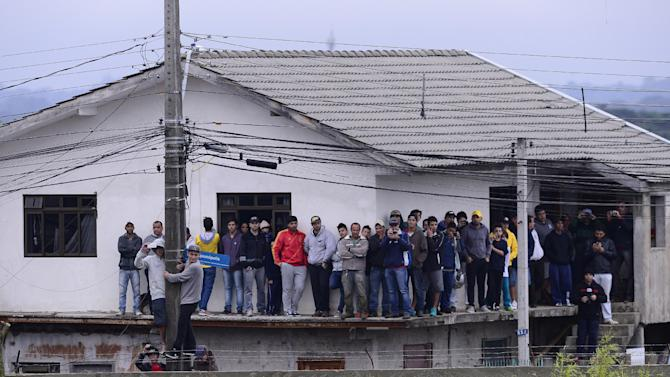 Spectators on a building's ledge, watch from a distance, Spain's national soccer team training in the Atletico Paranaense training center in Curitiba, Brazil, Tuesday, June 10, 2014. Spain will play in group B of the Brazil 2014 World Cup. (AP Photo/Manu Fernandez)