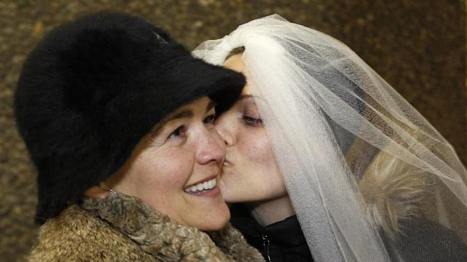 Amy Andrews, right, smiles as she wears a veil while kissing her partner Jeri Andrews while waiting to be among the first to be issued a marriage licenses to a same-sex couple, Wednesday, Dec. 5, 2012, in Seattle. King County Executive Dow Constantine was to began issuing the licenses just after midnight, immediately upon certification of the November election that passed Referendum 74 allowing same-sex couples to wed. Amy Andrews wore the same veil during a symbolic, though not legal, marriage ceremony the couple had in 2011. (AP Photo/Elaine Thompson)