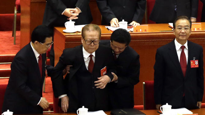 In this photo taken Thursday, Nov. 8, 2012, former Chinese President Jiang Zemin, second from left, is helped by Chinese President Hu Jintao, left, as Chinese Premier Wen Jiabao, right, stands for the national anthem during the opening session of the 18th Communist Party Congress at the Great Hall of the People in Beijing. (AP Photo/Ng Han Guan)