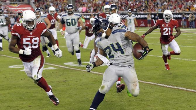 Seattle Seahawks running back Marshawn Lynch (24) tries to avoid Arizona Cardinals inside linebacker Daryl Washington (58) during the second half of an NFL football game, Thursday, Oct. 17, 2013, in Glendale, Ariz. (AP Photo/Ross D. Franklin)