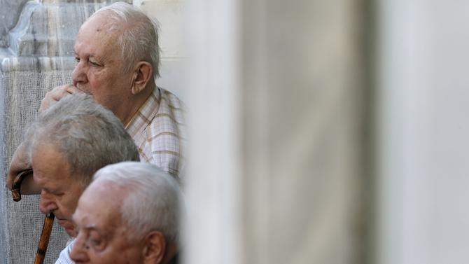 Pensioners sit on the steps outside a National Bank branch in Athens