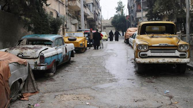 Vintage cars that belong to Mohamed Badr al-Din are seen along a street where he keeps them, in the al-Shaar neighborhood of Aleppo