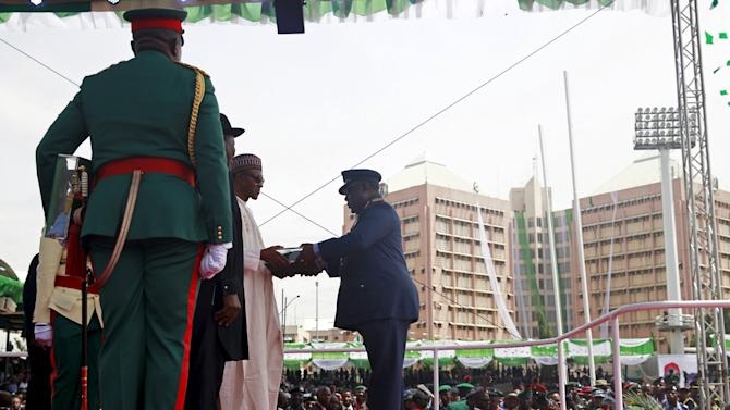 Nigeria's new President Muhammadu Buhari receives the flag of office from Chief of the Defence Staff, Air Marshal Alex Badeh at Eagle Square in Abuja