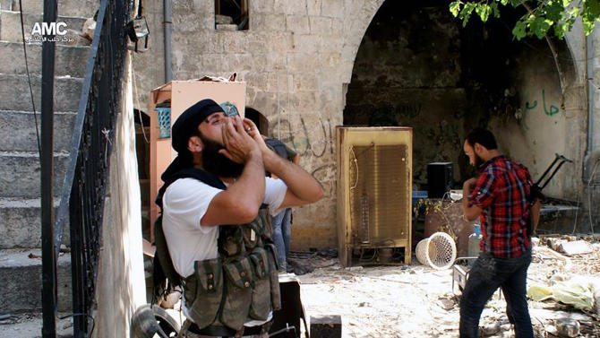 """This Tuesday, June 18, 2013 citizen journalism image provided by Aleppo Media Center AMC, which has been authenticated based on its contents and other AP reporting, shows a Syrian rebel shouting """"Allahu Akbar"""" (God is Great) in the Old City of Aleppo, Syria. A group of U.S. Senators want to see the U.S. do more than provide arms to some of the outgunned rebels in the bloody civil war in Syria. Democratic Sens. Robert Menendez and Carl Levin and Republican John McCain say in a joint letter to Obama that the U.S. should consider targeting regime airfields, runways and aircraft, and help rebels establish safe zones in Syria. (AP Photo/Aleppo Media Center AMC)"""