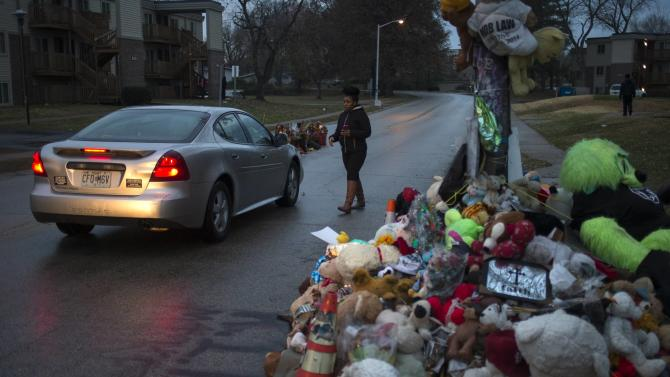 Visitor walks past a makeshift memorial at the site where Michael Brown was shot and killed in Ferguson, Missouri