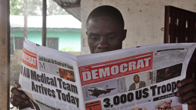 "A man reads a news paper with headlines comment on American President Barrack Obama announcement on sending troops to fight the Ebola virus in Monrovia, Liberia, Wednesday, Sept. 17, 2014. Liberia's president called Wednesday on the world to do more to end a spiraling Ebola outbreak, saying ""Liberia cannot defeat Ebola alone."" President Barrack Obama announced Tuesday that he will order 3,000 military personnel to West Africa to help contain the dreaded disease, which has killed at least 2,400 people. The U.S. is also planning on delivering 17 treatment centers with 100 beds each to Liberia, which has been hardest hit by the outbreak.  (AP Photo/Abbas Dulleh)"