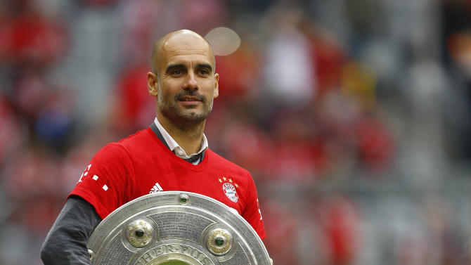 Bayern's head coach Pep Guardiola holds the trophy as his team celebrate winning the Bundesliga title after the German first division Bundesliga soccer match between FC Bayern Munich and FSV Mainz 05 at the Allianz Arena in Munich, Germany, Saturday, May 23, 2015. (AP Photo/Matthias Schrader)
